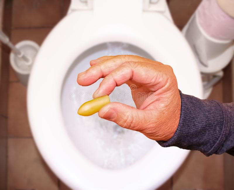 Suppository for constipation in the hand of an elderly person in the toilet against the background of the toilet bowl.  stock photography