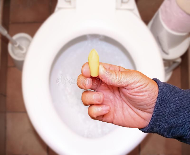 Suppository for constipation in the hand of an elderly person in the toilet against the background of the toilet bowl.  royalty free stock image