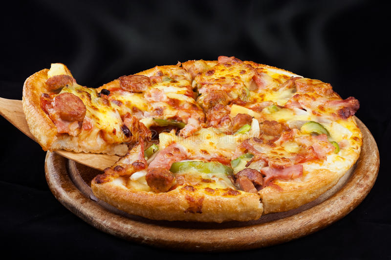 Supreme Hot Pizza. Lifted with black blackground royalty free stock photo