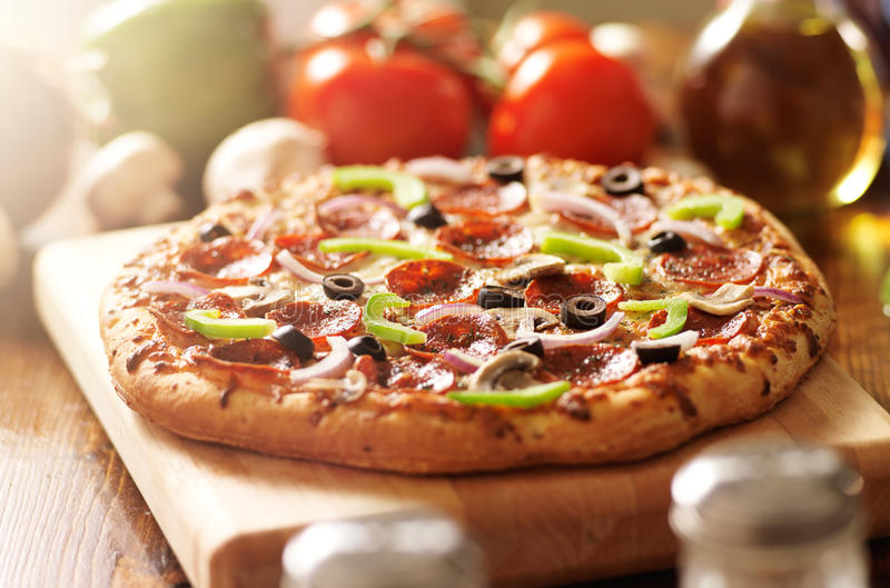 Supreme italian pizza with pepperoni and toppings. Photo of a supreme italian pizza with pepperoni and toppings and shot with selective focus royalty free stock photo