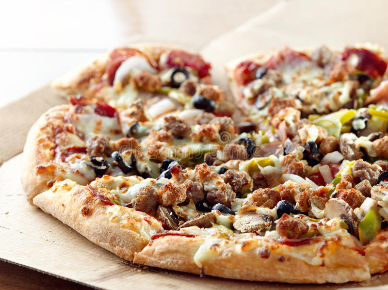 Supreme pizzza closeup. Closeup photo of a pizza with supreme toppings in a cardboard box stock photography