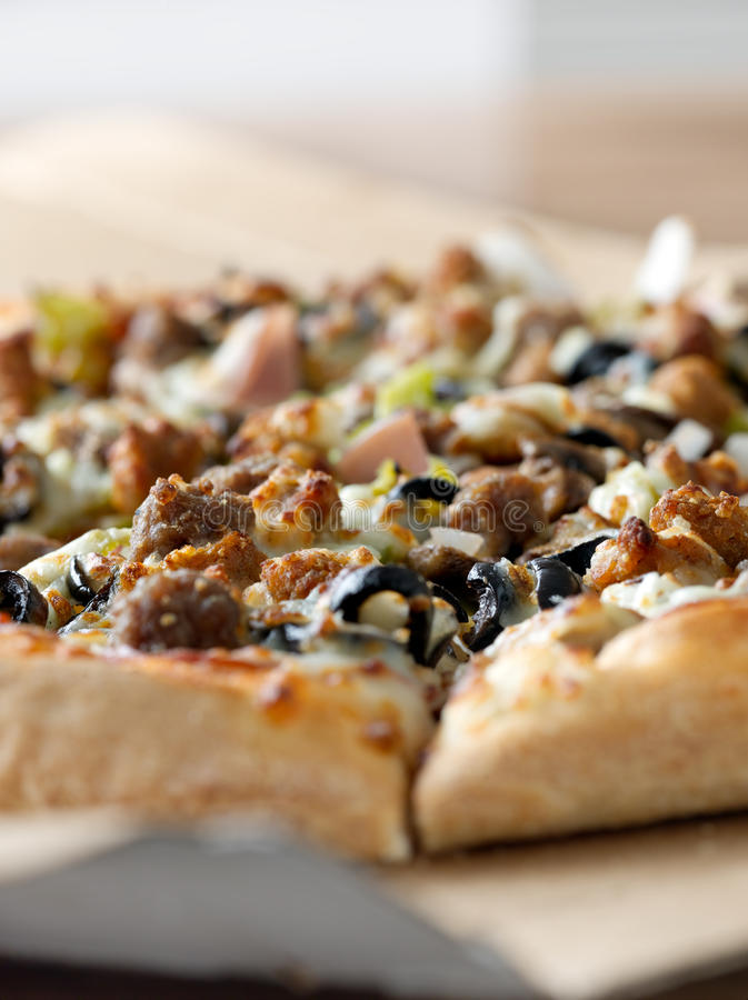 Supreme pizzza closeup. Closeup photo of a pizza with supreme toppings in a cardboard box royalty free stock images