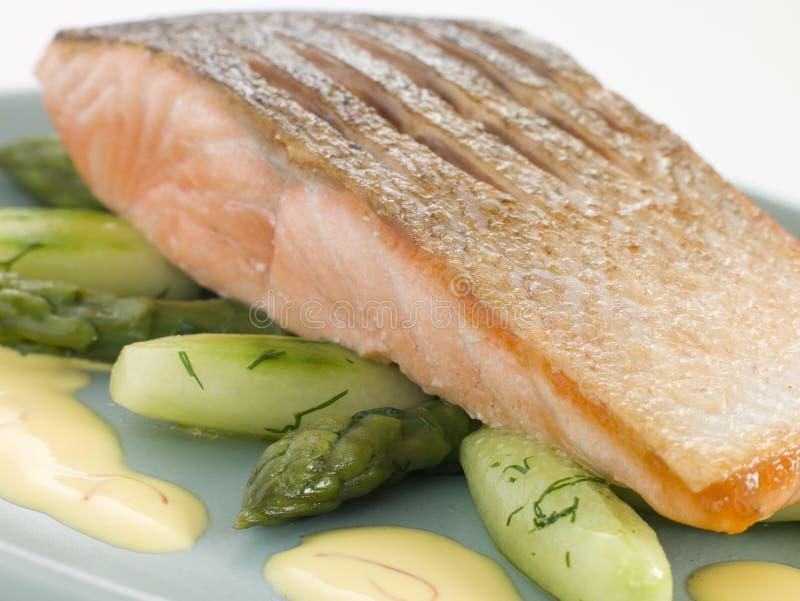 Supremo Salmon fritado torrado com espargos do pepino foto de stock