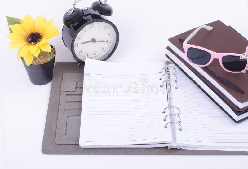 Sur l'article de table d'étudiant contenez l'horloge de vintage, plante de fleur artificielle et des journaux intimes d'empilemen photographie stock