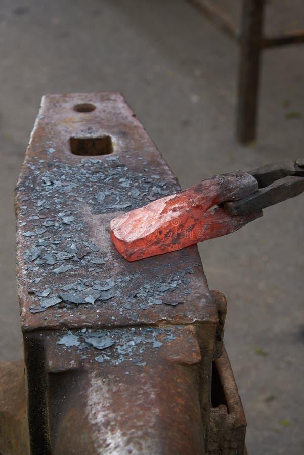 Sur l'enclume est une billette d'un rouge ardent en métal image stock