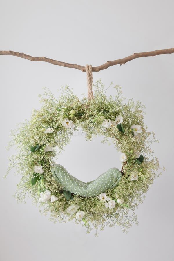 Sur la branche accroche un berceau d'anneau pour une séance photos des nouveaux-nés, un attrapeur rêveur, un arrangement floral a images stock
