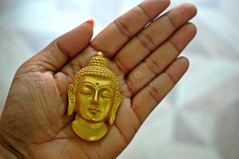 Sur la paume de la main est un Bouddha d'or font face images stock