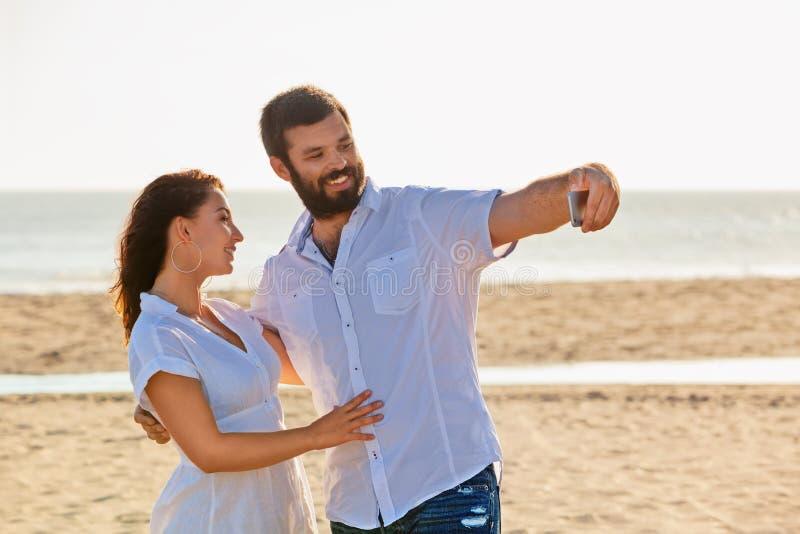 Sur la plage de mer les couples affectueux prennent le selfie par le téléphone portable image stock