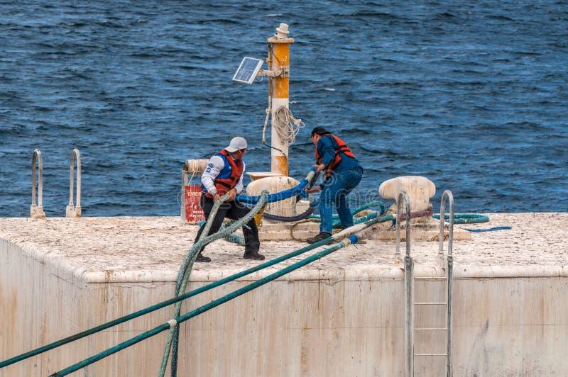 Sur la plate-forme d'amarrage les travailleurs moule le câble d'amarrage photo libre de droits