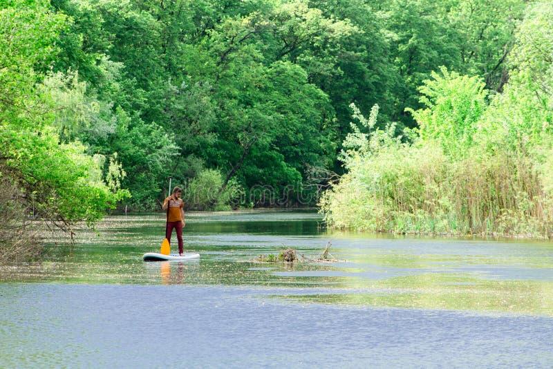 Sur la rivière dans la distance un homme nage sur un panneau de petite gorgée photo libre de droits