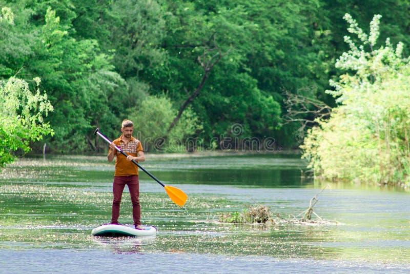 Sur la rivière dans la distance un homme nage sur un panneau de petite gorgée photo stock