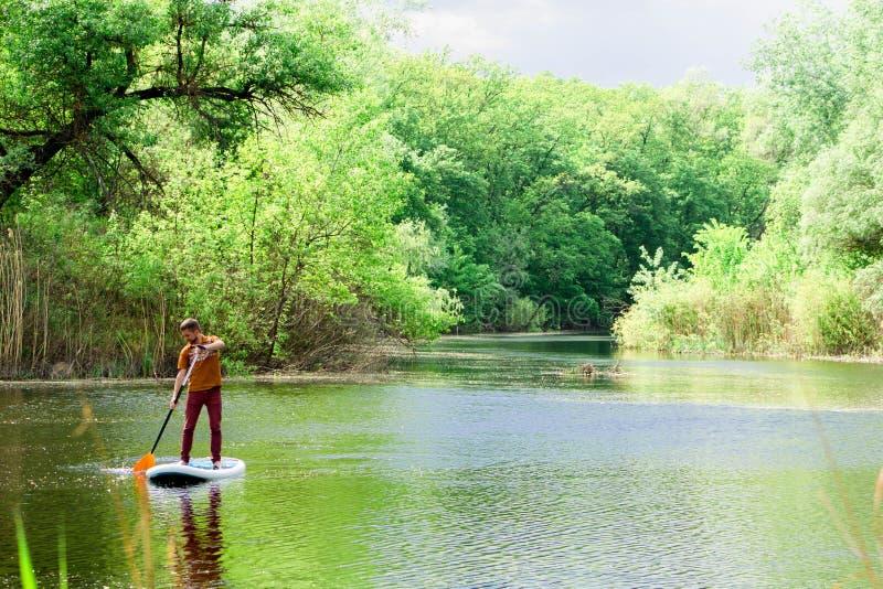 Sur la rivière dans la distance un homme nage sur un panneau de petite gorgée photos stock
