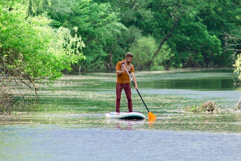 Sur la rivière dans la distance un homme nage sur un panneau de petite gorgée photographie stock libre de droits