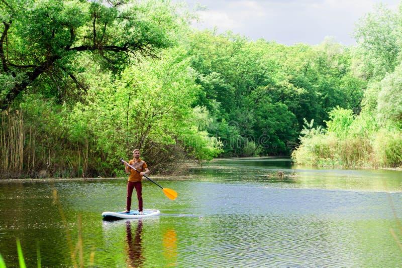 Sur la rivière dans la distance un homme nage sur un panneau de petite gorgée image stock