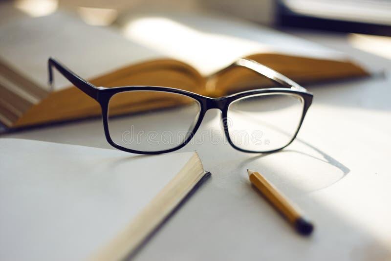 Sur la surface de la table sont un livre ouvert, un carnet ouvert, les verres et un crayon photo libre de droits