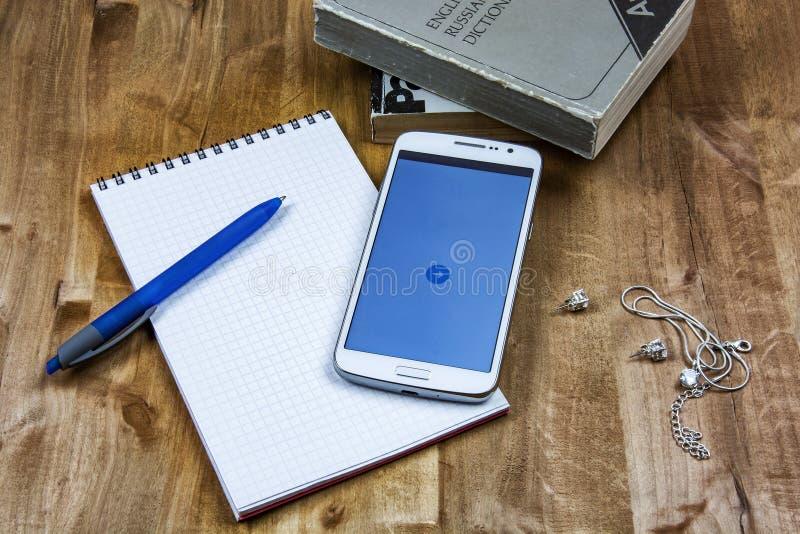 Sur la surface en bois sont les livres, un carnet avec un stylo, un smartp image stock
