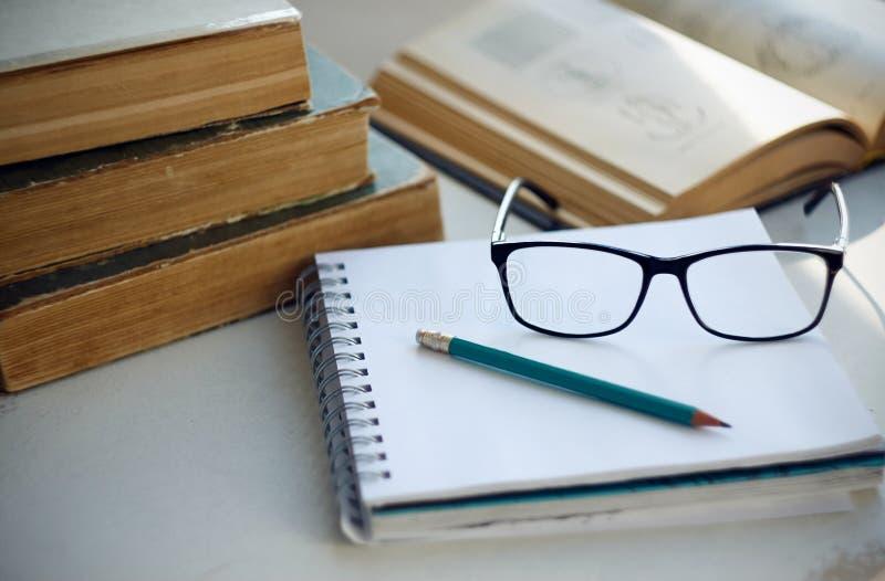 Sur la table étendez les encyclopédies, un carnet, le crayon, les verres et le livre avec des diagrammes photos libres de droits