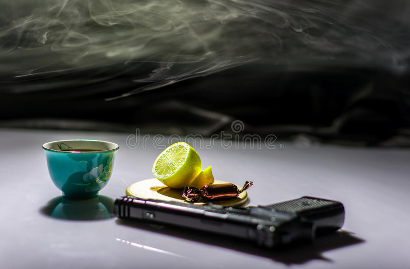 Sur la table une arme à feu et un thé avec le citron image stock