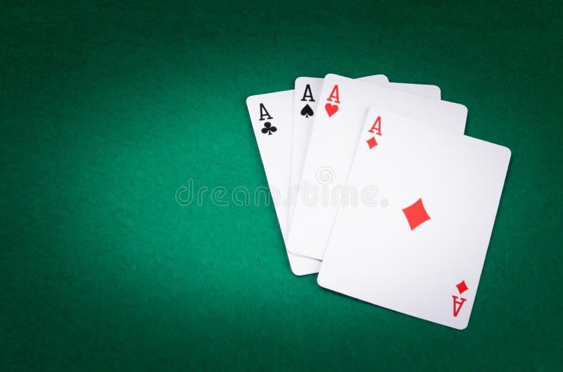Sur la table verte, un ensemble de quatre as est accentué, du côté gauche il y a un endroit pour l'inscription photo stock