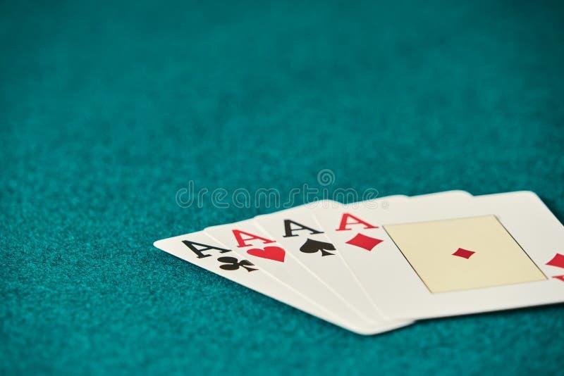 sur la table verte, un ensemble de quatre as se tient, ? la droite de l'image laissant le grand espace pour des inscriptions photographie stock libre de droits