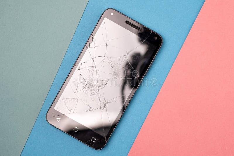 Sur la trois-couleur un fond est un smartphone cassé avec le verre cassé image libre de droits