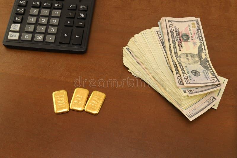 Sur le bureau sont les dollars d'argent liquide et les barres d'or Calculatrice images libres de droits