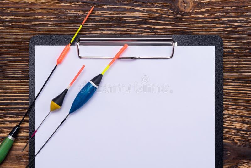 Sur le comprimé avec une bonne feuille sont les différents flotteurs pour une canne à pêche, un endroit pour votre inscription image stock