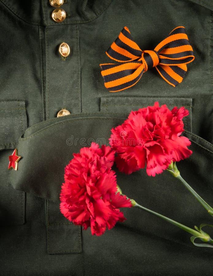 Sur le fond de l'habillement militaire, de deux oeillets rouges et du ruban de St George sous forme d'arc photographie stock