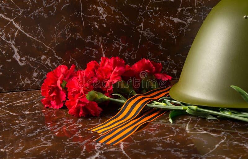 Sur le fond du monument, un bouquet des oeillets rouges, le casque militaire et le ruban de St George photographie stock