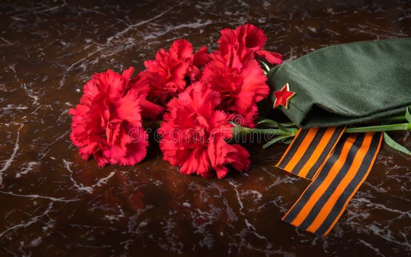 Sur le fond du monument, un bouquet des oeillets rouges, le chapeau militaire et le ruban de St George, plan rapproché photos stock