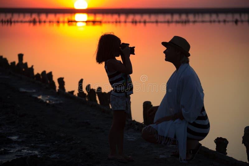 Sur le lac de sel une mère enseigne la fille à photographier des portraits photo stock