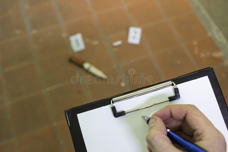 Sur le plancher carrelé se trouve un couteau et un mégot se plier, des preuves et enquête, main et stylo image libre de droits