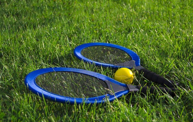 Sur les raquettes bleues du mensonge deux de pelouse d'herbe verte et une balle de tennis jaune images stock