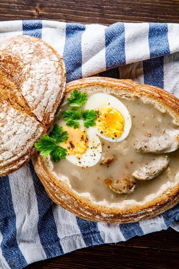 Sur rågsoppa i bröd på trätabellen royaltyfri foto