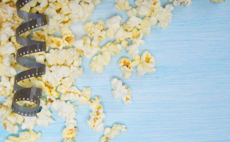 Sur un fond clair, avec l'espace pour l'inscription, le maïs éclaté dispersé et un morceau de film photo stock