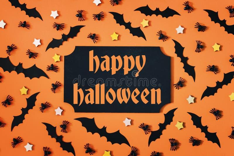 Sur un fond orange, il y a les battes, les araignées et les astérisques décoratifs Inscription au centre, Halloween heureux photographie stock libre de droits