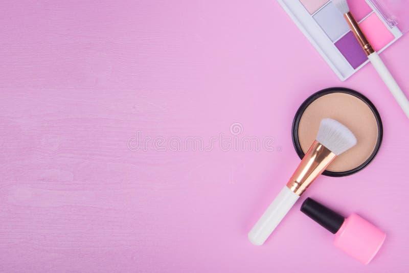 Sur un fond rose, avec un endroit pour une inscription, les articles pour le maquillage et la manucure, poudre pour lisser le tei photographie stock