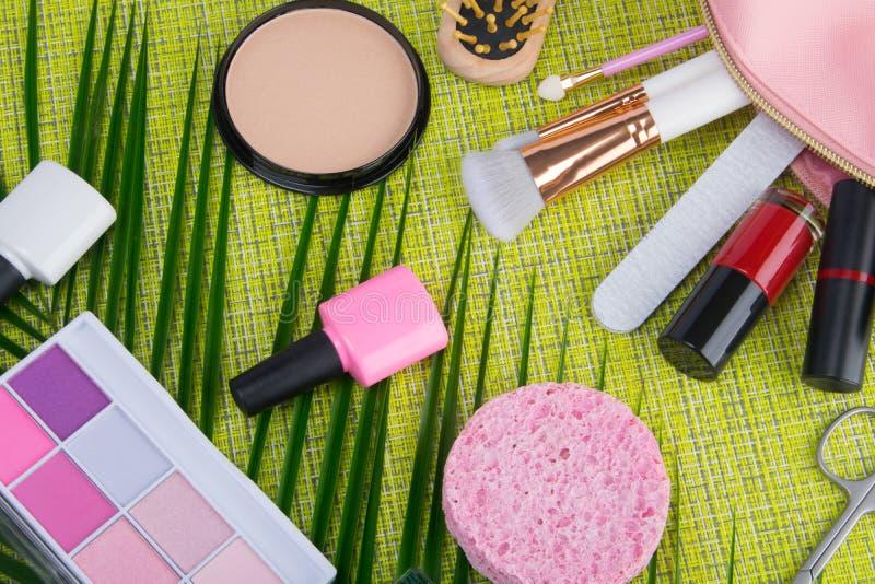 Sur un fond vert clair et des palmettes, dispersés dans les articles cosmétiques roses d'un maquillage de sac, brosse, vernis à o photo stock