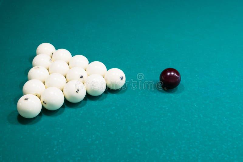 Sur un fond vert d'une table de billard, des boules blanches sont garnies d'une triangle photographie stock