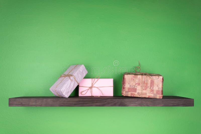 Sur un fond vert une étagère de couleur noire avec la texture du bois sur laquelle sont présentés en cadeaux année de rangée de n photo libre de droits