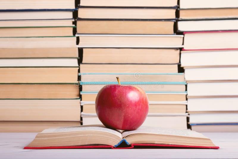 Sur un livre ouvert en livre à couverture dure il y a un rouge de pomme photographie stock