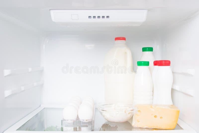 Sur une étagère dans des produits de réfrigérateur et animaux blancs, une crème, un lait, un képhir, un fromage d'oeuf et blanc e images libres de droits