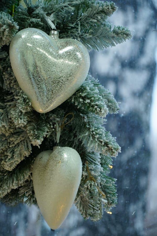 Sur une branche enneigée d'un arbre de Noël pendre les jouets du Nouvel An photographie stock