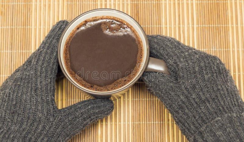 Sur une serviette en bois il y a une tasse avec du cacao, qui est tenu à la main dans des gants d'hiver photos stock