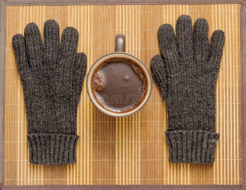 Sur une serviette en bois il y a une tasse de gants de cacao et d'hiver image stock