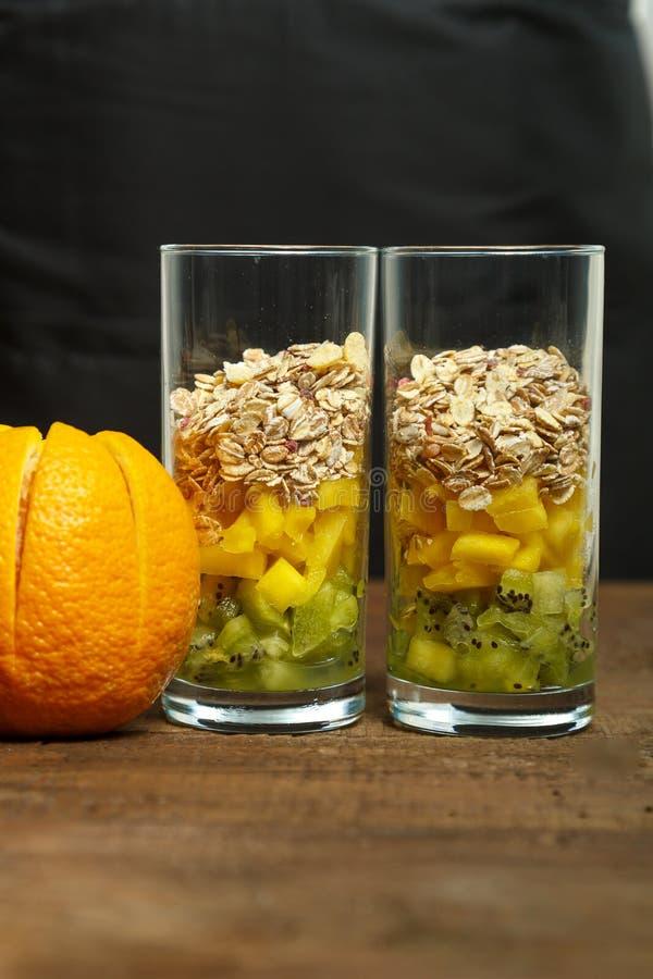 sur une table en bois sont deux verres avec des morceaux de fruit la porte à côté est une orange fraîche photographie stock