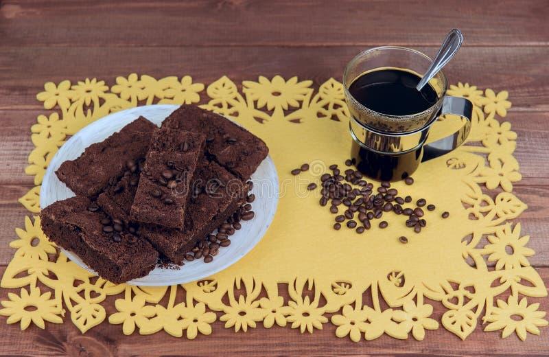 Sur une table en bois sur la tasse de serviette jaune de café en verre photographie stock libre de droits