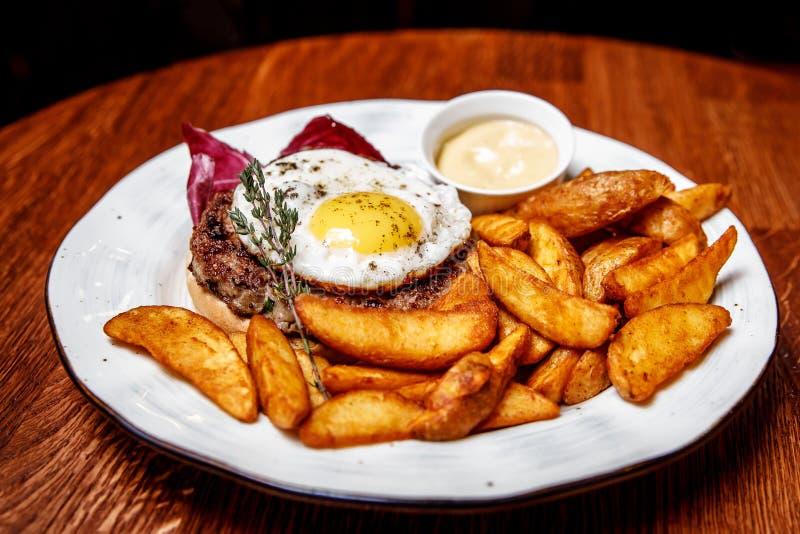 Sur une table en bois un plat avec le dîner : bifteck coupé avec l'oeuf, pommes de terre dans un style campagnard, sauce image libre de droits