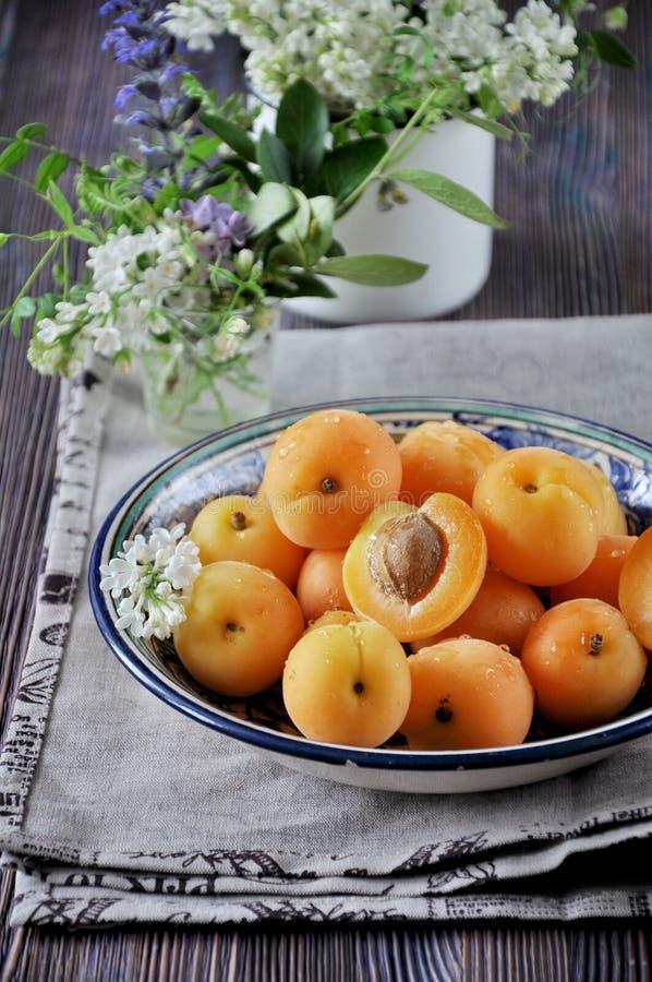 Sur une table en bois sur un plateau des abricots frais avec des os, décoré des fleurs image stock