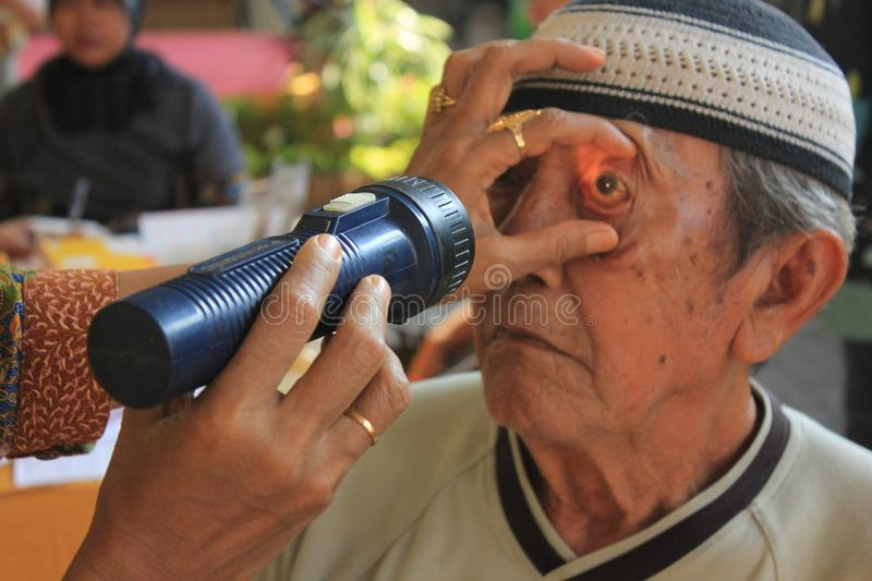 Surabaya indonesia, may 21, 2014. a health worker is checking the patient`s eyes. stock photos